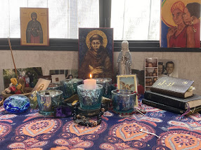 Home altar with candles and photos